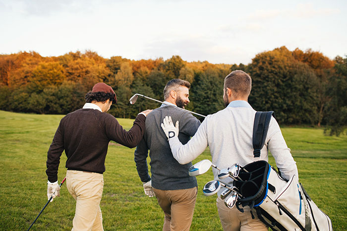 ゴルフ場で歩いている男性3人